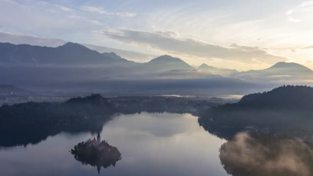 time lapse of lake bled, island and castle at sunrise - barocco video stock e b–roll