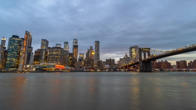 4K Time Lapse of Lower Manhattan Financial District cityscape river side with Brooklyn Bridge and East River in day to night time, New York City, United States, Architecture and landmark concept
