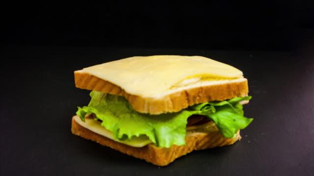 tidsfördröjning för att göra en stor smörgås med tomat, skinka, ost och sallad. stop-motion för att förbereda snacks. - cheese sandwich bildbanksvideor och videomaterial från bakom kulisserna
