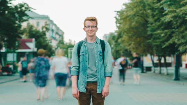 Time lapse of male tourist standing in city street on sidewalk looking at camera Time lapse of handsome male tourist standing in city street on sidewalk looking at camera while bypassers are walking around. People and society concept. redhead stock videos & royalty-free footage