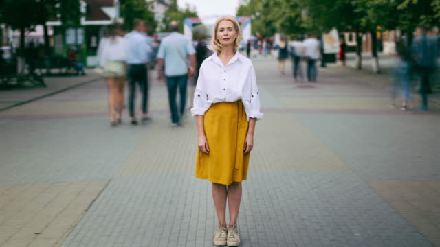 Video Time lapse of mature woman standing in city in busy street looking at camera