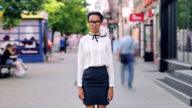 time lapse of mixed race girl standing in pedestrian street with serious face - tożsamość pojęcia filmów i materiałów b-roll