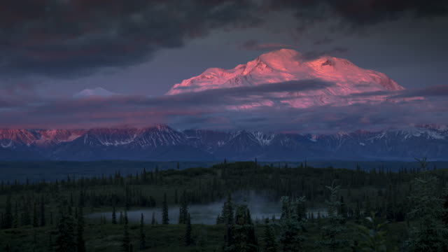 Time lapse of Mount Denali (McKinley) at sunrise, starts off pink and soon to be covered by clouds video