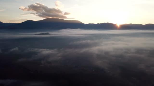 vídeos de stock e filmes b-roll de time lapse of mountain and sunrise , moving mist above the clouds - linha do horizonte sobre terra