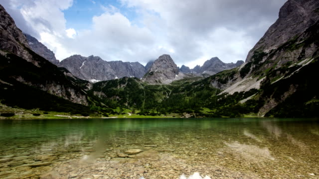 time lapse of mountains clouds and sunrays refection in alpine lake seebensee near ehrwald tirol tyrol austria europe alps landscape nature - stato federato del tirolo video stock e b–roll