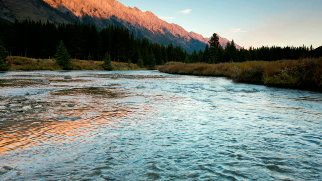 Time lapse of mountains glowing reflecting on alpine river video