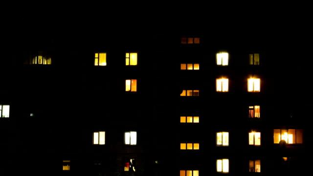 time lapse di multistorey edificio con cambiando finestra luci di notte - illuminato video stock e b–roll
