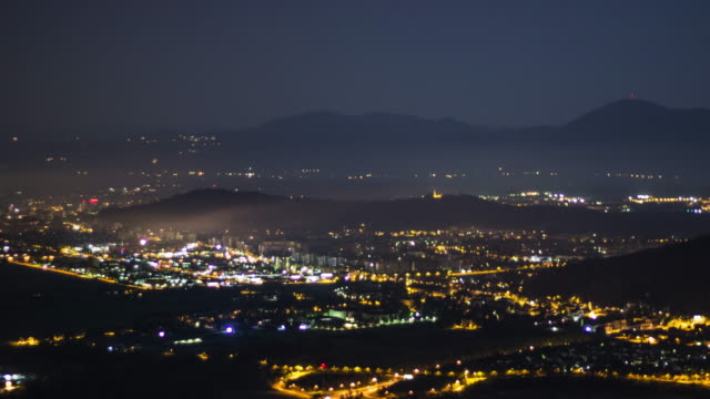 Time lapse of night life in city surrounded by mountains video
