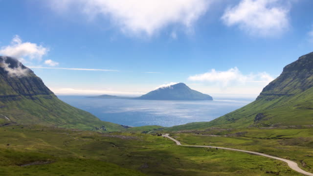 time lapse of nordredal valley in faroe islands, beautiful moving clouds from high mountains through shining atlantic ocean, blue sky and koltur island in the middle. - grass isolated video stock e b–roll