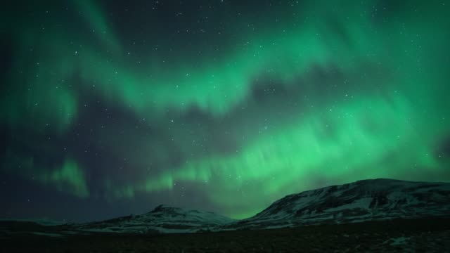 time lapse of northern light or polar light (aurora borealis) in the night sky over mountain landscape in winter of iceland - aurora boreale video stock e b–roll