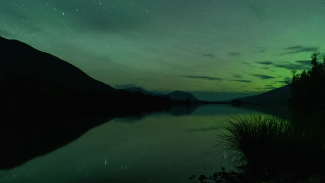 Time lapse of northern lights with reflection on lake in Alaska