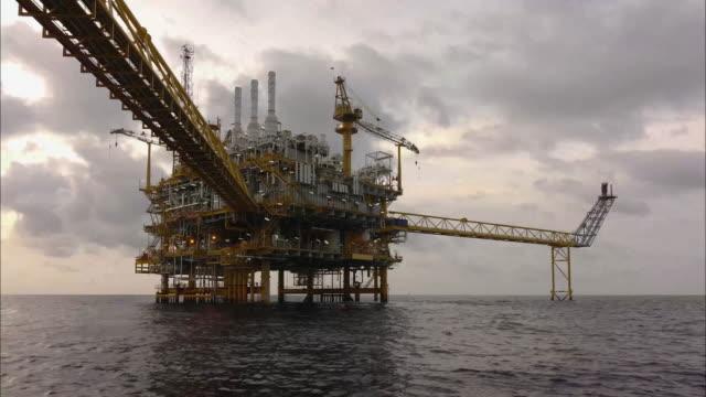 time lapse della piattaforma di elaborazione centrale offshore di petrolio e gas al tramonto. (nessun suono dell'ambiente) - brent video stock e b–roll