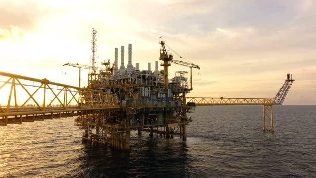 4K Time lapse of offshore oil and gas processing platform in sunset that produce natural gas and condensate for sent to onshore refinery and petrochemical plant. 4K Time lapse of offshore oil and gas processing platform in sunset that produce natural gas and condensate for sent to onshore refinery and petrochemical plant. oil and gas stock videos & royalty-free footage