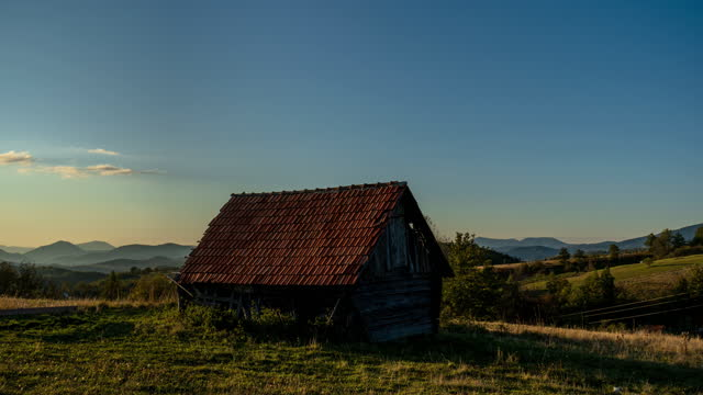 Time lapse of old house in mountain at sunset and sheeps in background, 4 K
