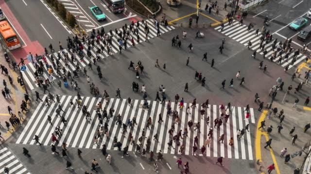 4k zeitraffer von fußgängern und auto menge undefinierte menschen zu fuß überqueren die straße kreuzung überqueren des bezirks shibuya bezirk tokyo stadt, japan. japanisches kultur- und einkaufsviertelkonzept - zeitraffer fast motion stock-videos und b-roll-filmmaterial