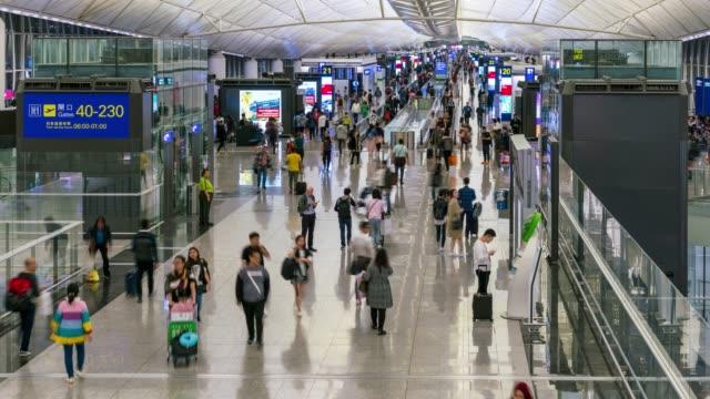 промежуток времени толпы людей в зоне вылета аэропорта в гонконге китай - аэровокзал стоковые видео и кадры b-roll