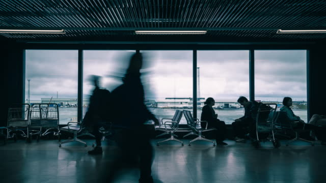 time lapse of people walking in the international airport at the departure gate. - аэровокзал стоковые видео и кадры b-roll