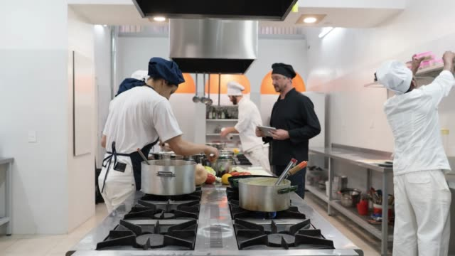 Time lapse of people working at a restaurant's kitchen all working on different orders to serve Time lapse of people working at a restaurant's kitchen all working on different orders to serve very focused commercial kitchen stock videos & royalty-free footage