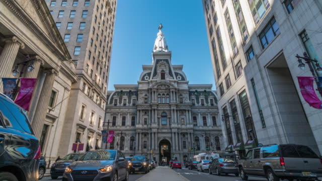 4K Time lapse of Philadelphia's landmark historic City Hall among building and car traffic light with blue sky, Pennsylvania, United States of America or USA, history and culture for travel concept