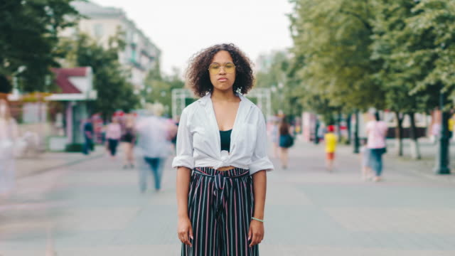 Video Time lapse of pretty Afro-American student standing in urban street outdoors