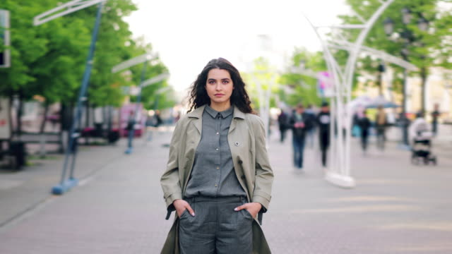 Time lapse of pretty girl standing in street hands in pockets looking at camera Time lapse of pretty girl standing in the city street with hands in pockets looking at camera with serious face while people are walking by. Person and society concept. stationary stock videos & royalty-free footage
