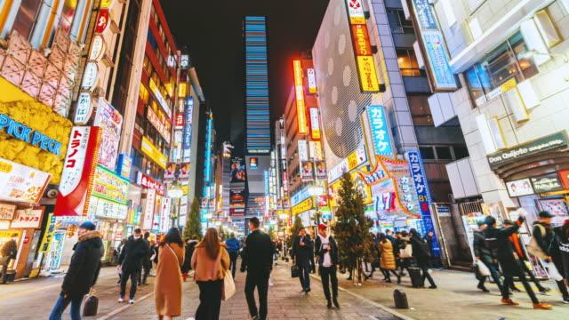 zeitraffer von shinjuku in der nacht mit menge undefinierte menschen auf der straße in tokio stadt, japan - zeitraffer fast motion stock-videos und b-roll-filmmaterial
