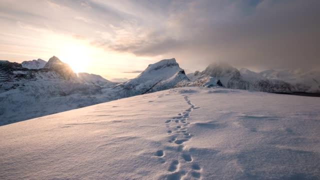 tidsfördröjning för av snöiga bergskedja med fotavtryck på snö på soluppgången morgonen - bergsrygg bildbanksvideor och videomaterial från bakom kulisserna