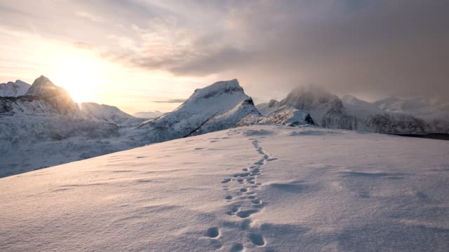 time lapse of snowy mountain range with footprint on snow at sunrise morning - traccia video stock e b–roll