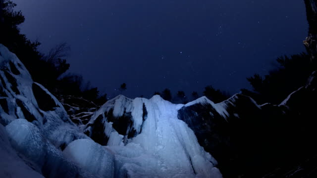 """vídeos de stock e filmes b-roll de time lapse of starry sky over the frozen waterfall in the siberian forest. krasnoyarsk nature reserve """"stolby"""". - sibéria"""