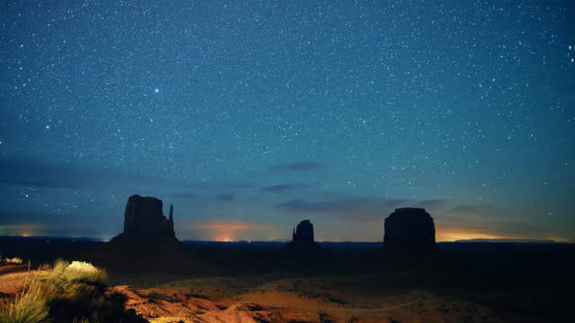 vídeos y material grabado en eventos de stock de time lapse of stars and shooting stars in the night sky with silhouettes of rock formations in the distance in the monument valley desert in utah/arizona at night - paisaje espectacular