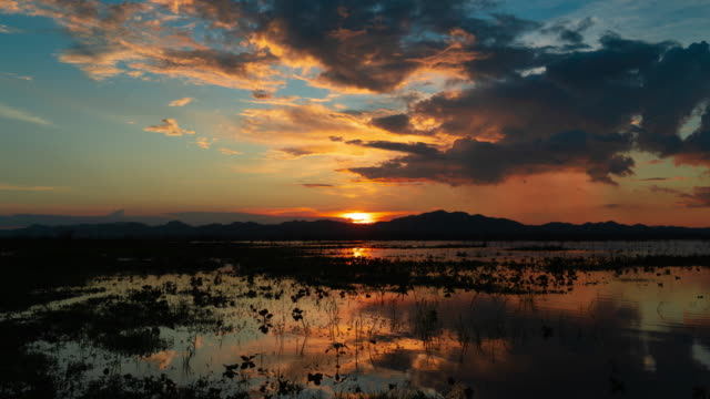 time lapse of sun goes down time lapse of sun goes down behind mountain included glow orange ray light reflect to cloud and raining in tail of cloud wetland stock videos & royalty-free footage