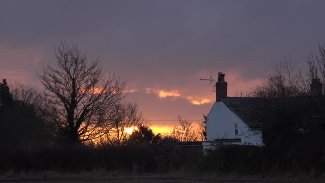 time lapse di sole che tramonta su cottage uk 4k - alba crepuscolo video stock e b–roll