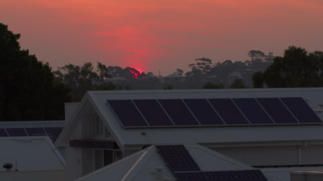 vídeos de stock e filmes b-roll de time lapse of sun rising over suburban neighbourhood, showing roof tops with solar panels installed. rising adoption and acceptance metaphor. pink sun caused by pollution and smoke. - solar panel