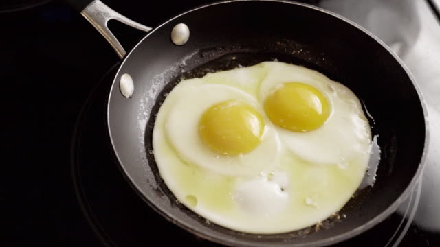 time lapse of sunny side ägg stekning i en stekpanna på en spis i ett kök - frying pan bildbanksvideor och videomaterial från bakom kulisserna
