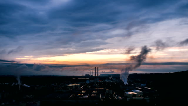time lapse of sunrise above cardboard and paper mill. - centrale termoelettrica video stock e b–roll