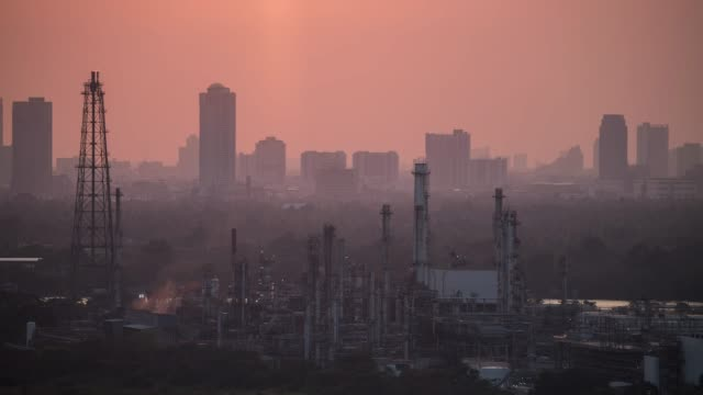 time lapse of sunset over oil refinery factory with large city in the background. - cartello economico video stock e b–roll