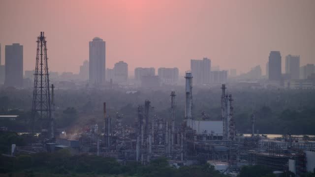time lapse of sunset over oil refinery factory with large city in the background. - opec video stock e b–roll