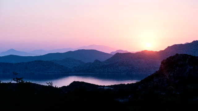 time lapse of sunset view of mountains and sea - morze egejskie filmów i materiałów b-roll