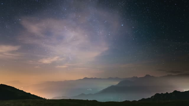 time lapse of the milky way rotating over the alps with fog - physics stock videos and b-roll footage