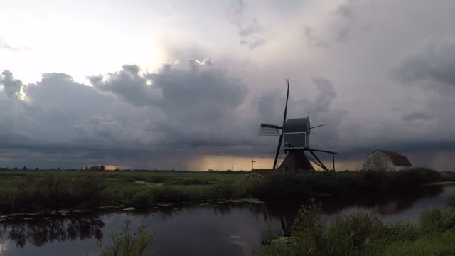 Time lapse of the motion of upcoming storm clouds over a windmill Dramatic storm clouds are approaching over a classic dutch polder landscape with windmill. dutch architecture stock videos & royalty-free footage
