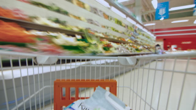 Time Lapse of the Shopping Cart Moving Between Various Aisles and Section in the Big Supermarket. Inside Trolley Various Healthy Items and Convenience Food. Time Lapse of the Shopping Cart Moving Between Various Aisles and Section in the Big Supermarket. Inside Trolley Various Healthy Items and Convenience Food. Shot on RED EPIC-W 8K Helium Cinema Camera. shopping cart stock videos & royalty-free footage