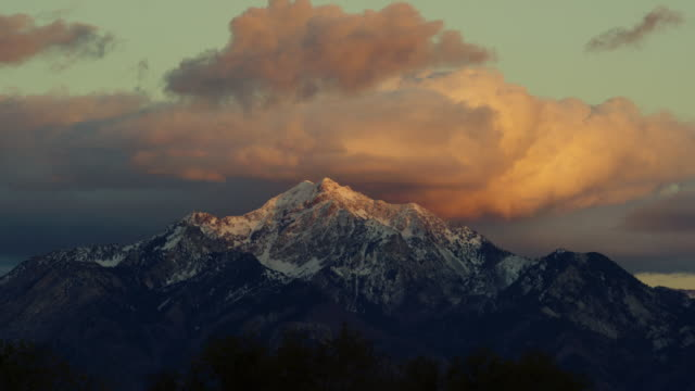 time lapse of the snowcapped wasatch mountains above salt lake city, ut at sunrise/sunset with a dramatic cloudscape - utah video stock e b–roll