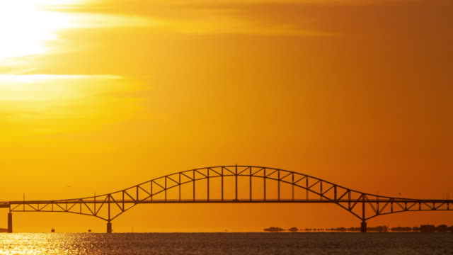 Time lapse of the sun setting behind a steel tied arch bridge, with silhouettes of cars traveling across the bridge, and boats sailing through the water.