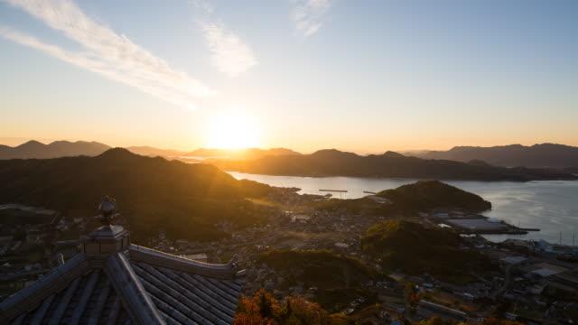 zaman atlamalı güneş ayarı sona kıyısında bir balıkçı köyü - hiroshima stok videoları ve detay görüntü çekimi