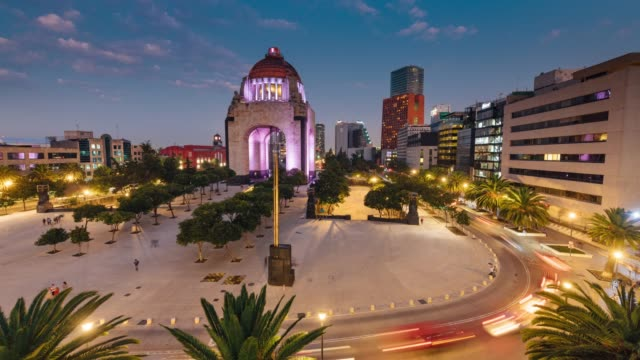 time lapse of the traffic circling revolution monument in mexico city - город мехико стоковые видео и кадры b-roll
