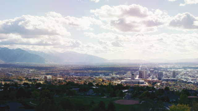 time lapse of the utah state capital and downtown salt lake city with the wasatch mountains in the background under a partially cloudy sky - salt lake stan utah filmów i materiałów b-roll
