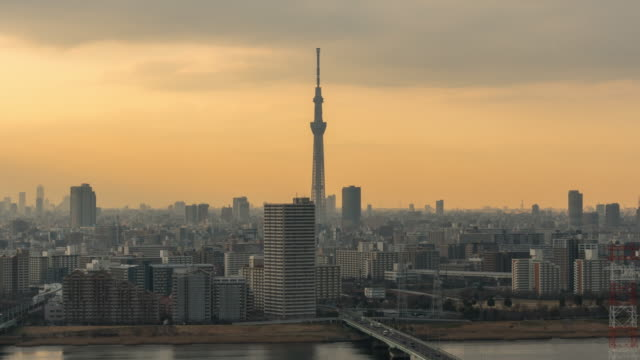4K Time lapse of Tokyo Skytree locate with various building cityscape and traffic road intersection in rush hour at sunset time which have sunbeam from Tower Hall Funabori Observation tower, Japan