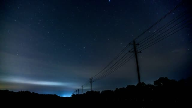 Time Lapse of Traffic on Small Country Road Illuminating the Utility Post With Stars Moving in the Background