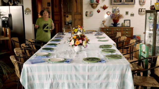 Time lapse of two women setting a large table for a dinner party