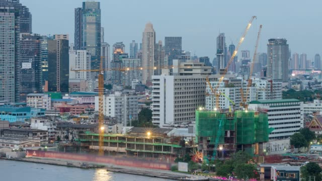 Time lapse of Under construction, Cranes built the building of bangkok cityscape river side on day to night, Thailand, 4k clip